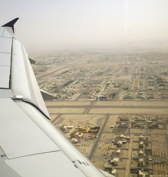 Qatar Airways flying over Abu Dhabi houses