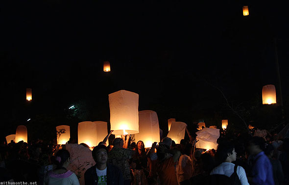 People lighting lanterns at Mae Jo