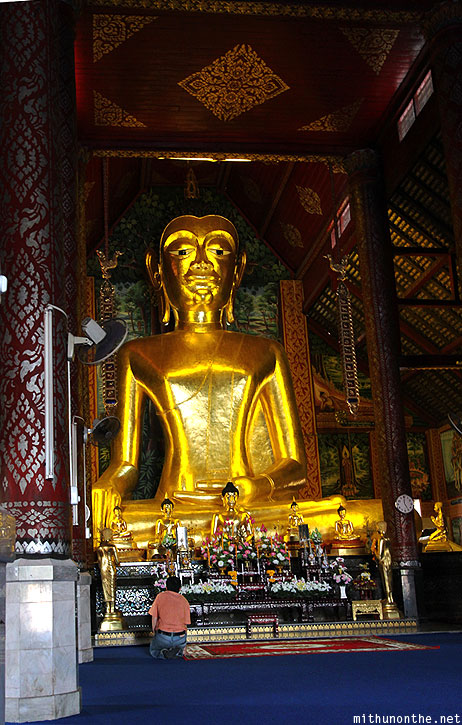 Wat Jedyod golden buddha statue man praying Chiang Rai