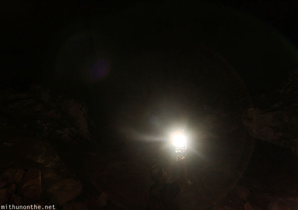 Inside Sumaguing cave guide holding lantern light