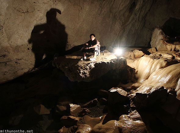 Inside sumaguing cave guide sitting limestone rock