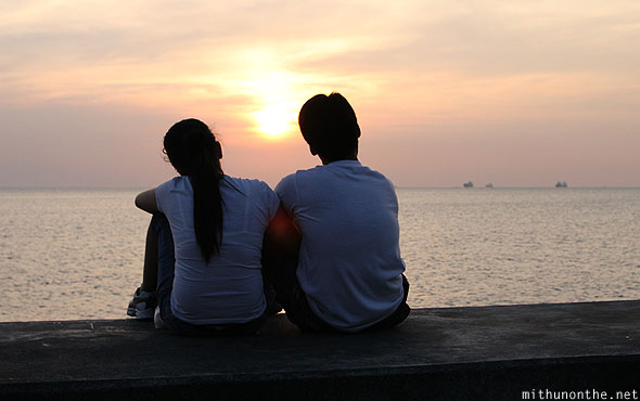 Filipino couple watching sunset Manila baywalk Philippines