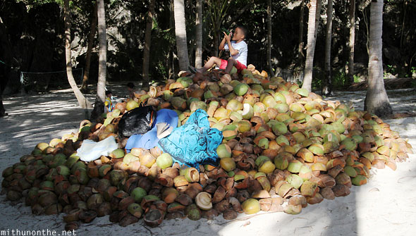Boy sitting on coconut drinking cola 7 Commandos island El Nido Philippines