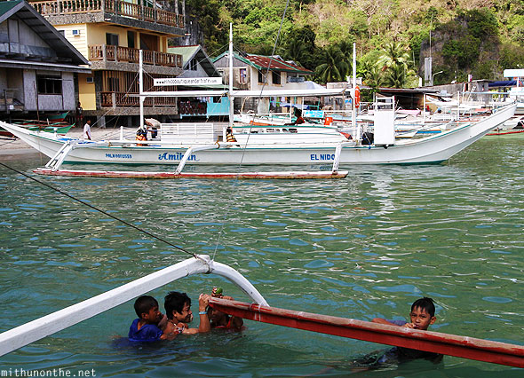 El Nido outrigger boat Filipino boys holding on Palawan