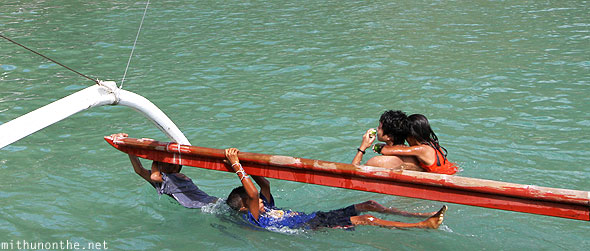 El Nido outrigger boat local boys holding on Palawan