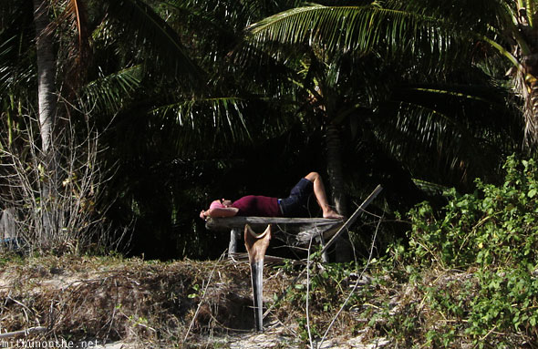 Tourist lying on bench 7 commandos beach El Nido Palawan Philippines