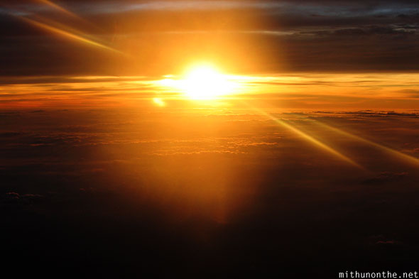 Evening sunset from airplane above clouds India