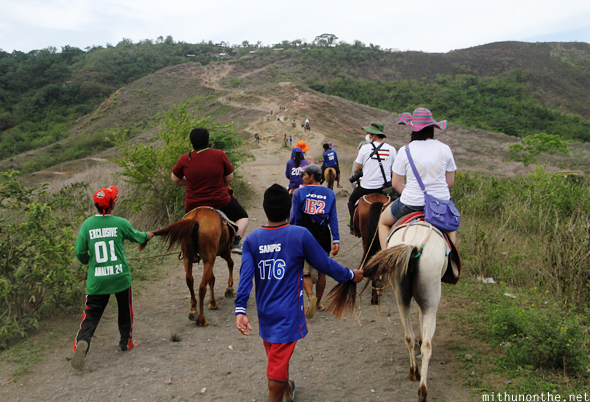Riding horses Taal volcano island Philippines