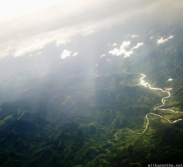 Sun rays over green hills Philippines from sky