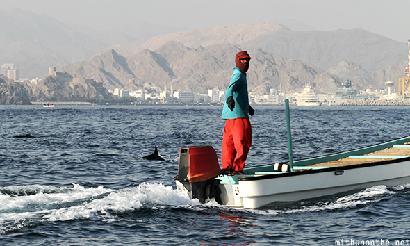 Fisherman feeding dolphins Oman