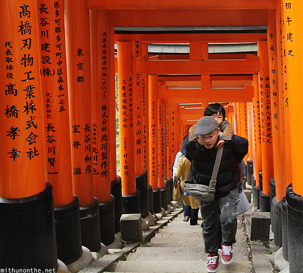 Parent carrying child climbing Fushimi Inari
